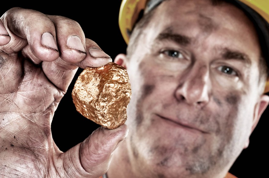 A gold miner shows a golden hugget freshly excavated from a mine.