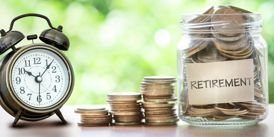 Hand putting Coins in glass jar with retro alarm clock  for time to money saving for retirement concept